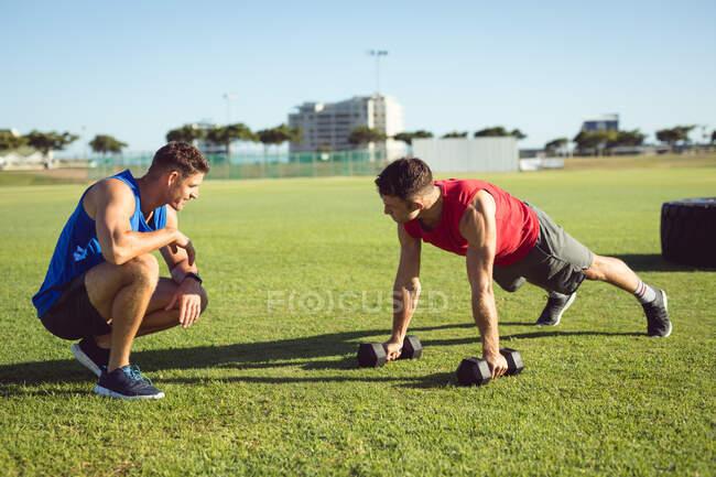 Белый мужчина и тренер тренируются на улице, отжимаются, держа гантели. здоровый активный образ жизни, кросс тренировки для фитнеса. — стоковое фото