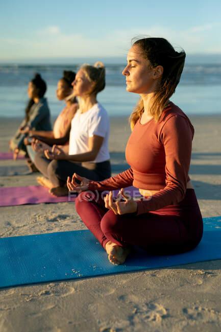 Группа разнообразных подруг, практикующих йогу, медитирующих на пляже. здоровый активный образ жизни, фитнес на открытом воздухе и благополучие. — стоковое фото