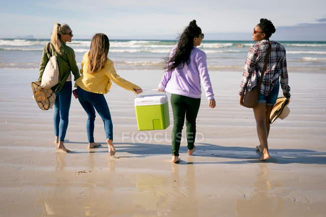 Felice gruppo di diverse amiche che si divertono, passeggiando lungo la spiaggia ridendo. vacanze, libertà e tempo libero all'aria aperta. — Foto stock