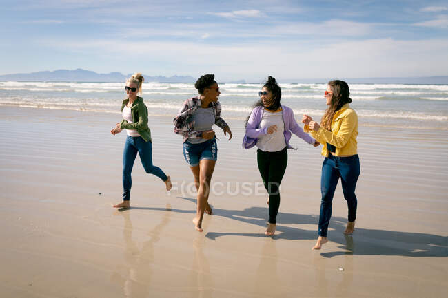 Feliz grupo de diversas amigas divirtiéndose, caminando por la playa y riendo. vacaciones, libertad y tiempo libre al aire libre. - foto de stock