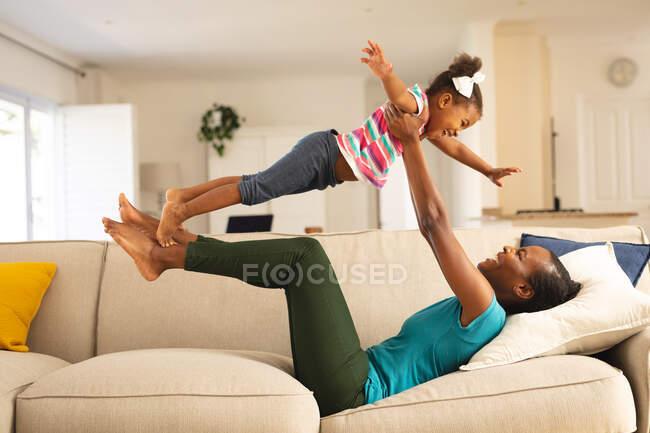 Feliz madre afroamericana acostada en el sofá divirtiéndose balanceando a su hija sonriente por encima de ella. familia pasar tiempo juntos en casa. - foto de stock