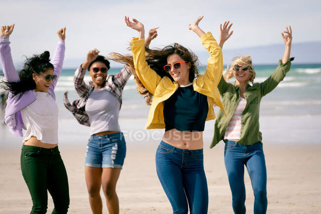 Felice gruppo di diverse amiche che si divertono, passeggiando lungo la spiaggia tenendosi per mano e ridendo. vacanze, libertà e tempo libero all'aria aperta. — Foto stock