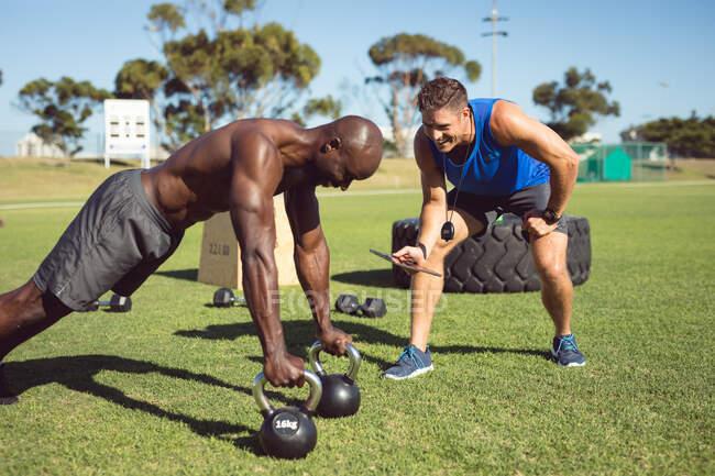 Африканський американський мускулистий чоловік тренувався надворі з дзвінками чайників і інструктором з фітнесу. Здоровий активний спосіб життя, перехресна підготовка до фітнесу. — стокове фото