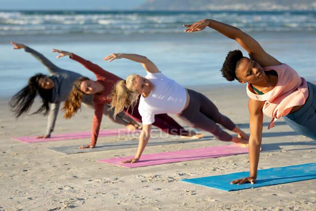 Группа разнообразных подруг практикующих йогу, опирающихся на одну руку, растянутую на пляже. здоровый активный образ жизни, фитнес на открытом воздухе и благополучие. — стоковое фото