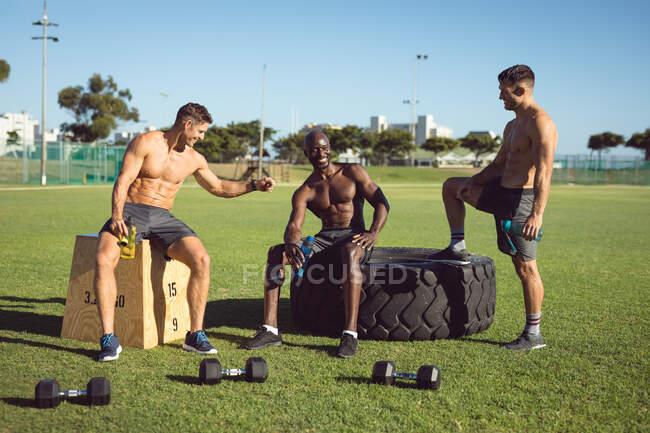 Разнообразная группа счастливых мужчин без рубашки, тренирующихся на улице, берущих перерыв в разговорах и кулаках. здоровый активный образ жизни, кросс тренировки для фитнеса. — стоковое фото