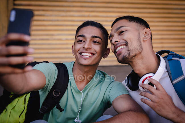 Two happy mixed race male friends with backpacks sitting in city street taking selfie and smiling. backpacking holiday, city travel break. — Stock Photo