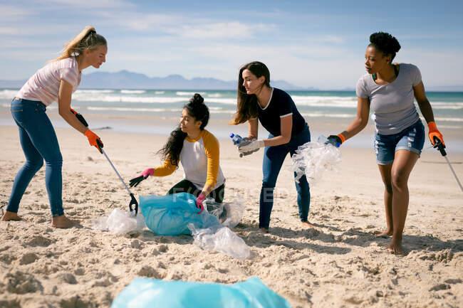 Різна група подруг забирає сміття з пляжу. Добровольці з охорони екології, прибирання пляжів.. — стокове фото