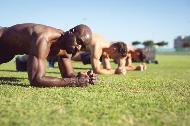 Разнообразная группа мускулистых мужчин, занимающихся досками на открытом воздухе. здоровый активный образ жизни, перекрестные тренировки для фитнеса. — стоковое фото