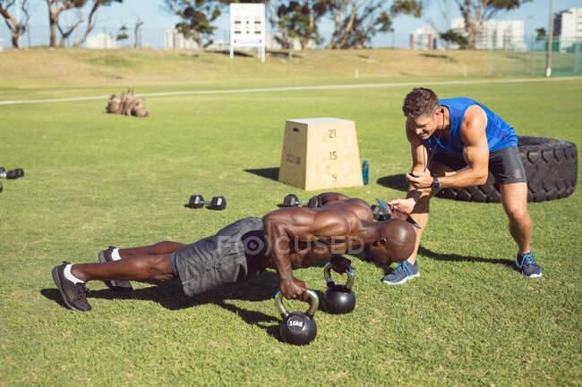 Hombre musculoso afroamericano haciendo ejercicio al aire libre con campanas de tetera e instructor de fitness. estilo de vida activo saludable, entrenamiento cruzado para fitness. - foto de stock