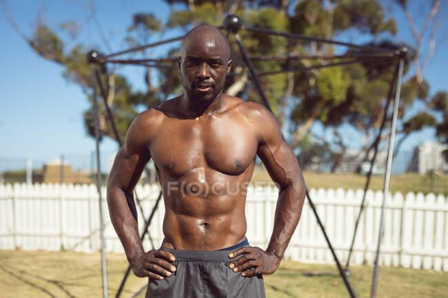 Portrait eines fitten afrikanisch-amerikanischen Mannes, der im Freien trainiert und eine Pause im Stehen am Übungsrahmen einlegt. gesunder aktiver Lebensstil, Crosstraining für Fitness. — Stockfoto