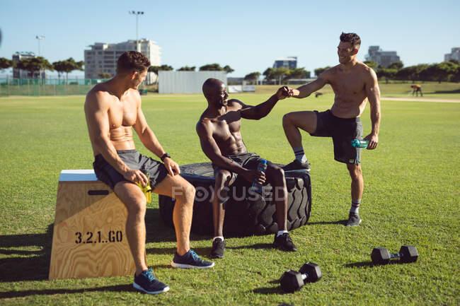 Разнообразная группа счастливых мужчин без рубашек, тренирующихся на улице, берущих перерыв, разговаривающих и бьющих кулаками. здоровый активный образ жизни, кросс тренировки для фитнеса. — стоковое фото