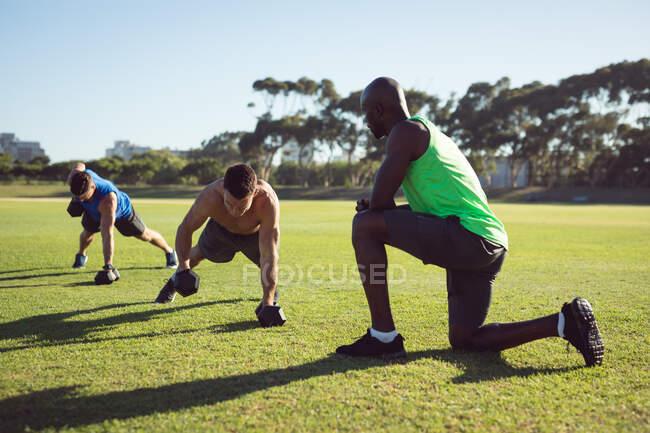 Подходит разнообразная группа мужчин, тренирующихся на открытом воздухе, один инструктирует, в то время как два лифта гантели. здоровый активный образ жизни, кросс тренировки для фитнеса. — стоковое фото