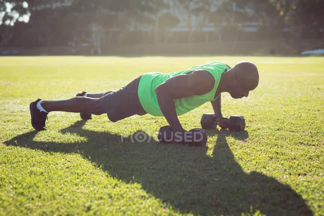 Африканський американський мускулистий чоловік, що бігає надворі з тупиками. Здоровий активний спосіб життя, перехресна підготовка до фітнесу. — стокове фото