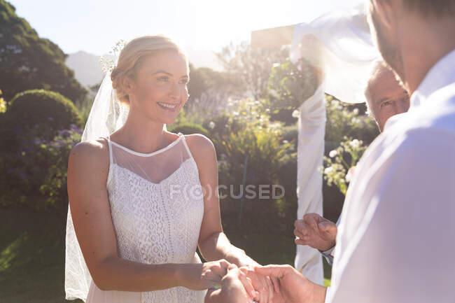 Feliz novia caucásica y novio casarse tomados de la mano jurando. boda de verano, matrimonio, amor y concepto de celebración. - foto de stock