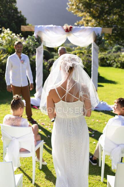Feliz novia caucásica y novio casarse en el jardín soleado. boda de verano, matrimonio, amor y concepto de celebración. - foto de stock
