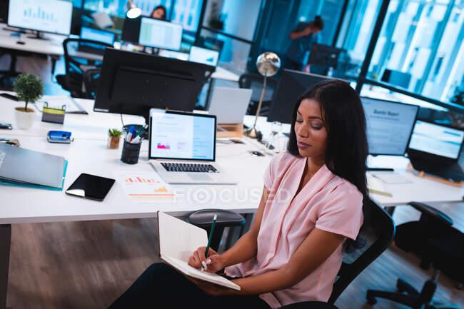Empresaria mixta sentada a la mesa y tomando notas con colegas de fondo. trabajar en una oficina moderna. - foto de stock