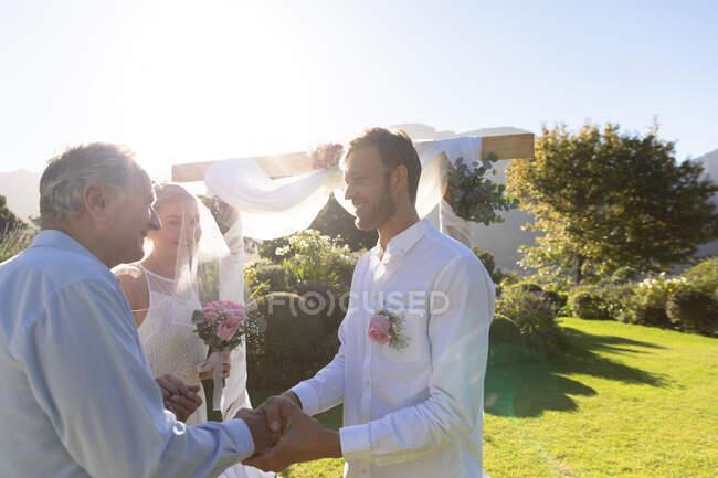 Feliz novia caucásica y novio casarse estrechando la mano con oficiante de la boda. boda de verano, matrimonio, amor y concepto de celebración. - foto de stock