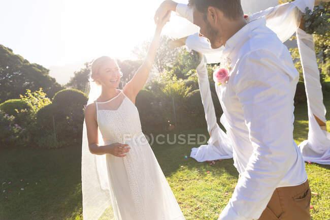 Feliz novia caucásica y novio casarse y bailar. boda de verano, matrimonio, amor y concepto de celebración. - foto de stock