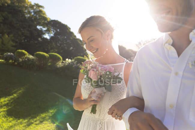 Feliz novia caucásica y novio casarse y sonreír. boda de verano, matrimonio, amor y concepto de celebración. - foto de stock