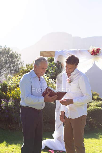 Novio caucásico casarse y hablar con el oficiante de la boda. boda de verano, matrimonio, amor y concepto de celebración. - foto de stock