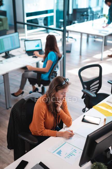 Кавказька бізнесменка записує і сидить за столом з колегами на задньому плані. працювати в сучасному офісі.. — стокове фото