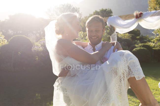 Novia caucásica feliz y novio casarse, novio llevar novia. boda de verano, matrimonio, amor y concepto de celebración. - foto de stock