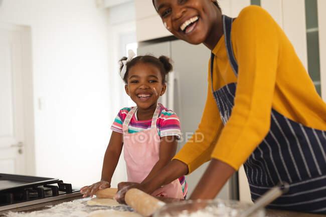 Sonriente madre afroamericana y su hija horneando en la cocina rodando masa juntos. familia pasar tiempo juntos en casa. - foto de stock