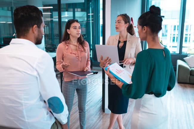 Groupe de gens d'affaires divers discutant ensemble et détenant des documents et un ordinateur portable. travailler dans un bureau moderne. — Photo de stock