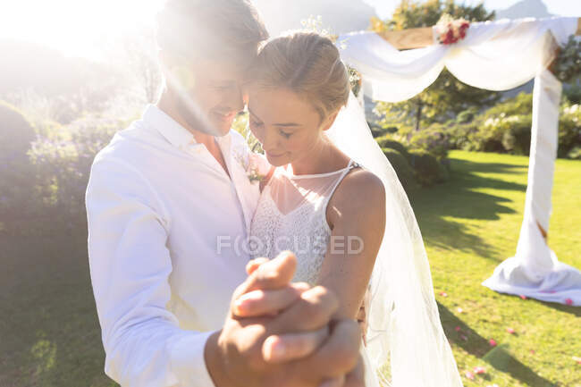 Feliz novia caucásica y novio casarse y tomarse de la mano. boda de verano, matrimonio, amor y concepto de celebración. - foto de stock