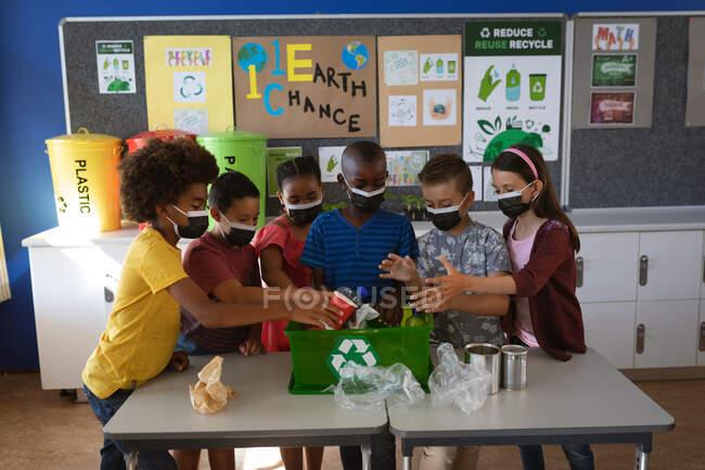Grupo de estudiantes diversos que usan máscaras faciales que ponen artículos plásticos reciclables en bandeja en la escuela. educación volver a la escuela seguridad sanitaria durante la pandemia de coronavirus covid19. - foto de stock