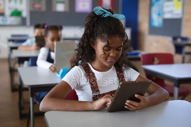 Chica afroamericana usando tableta digital mientras está sentada en su escritorio en la clase en la escuela. escuela y concepto de educación - foto de stock