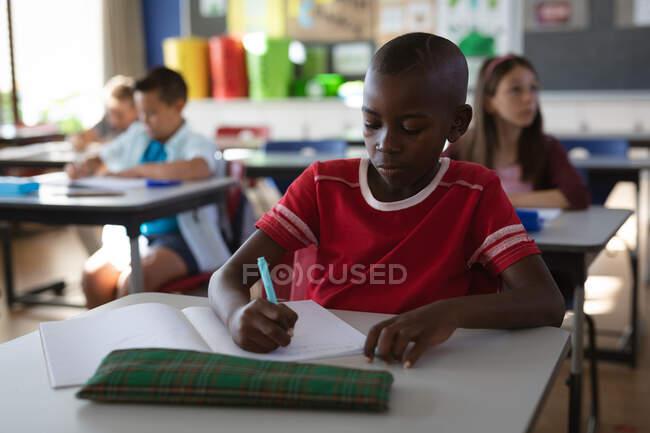 Niño afroamericano estudiando mientras está sentado en su escritorio en la clase de la escuela. escuela y concepto de educación - foto de stock
