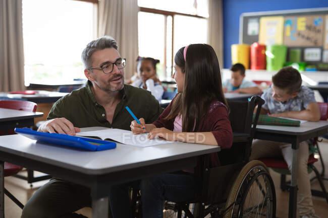 Кавказька вчителька чоловічої статі, яка навчає інвалідності, сидить на інвалідному візку в школі. школа і освіта — стокове фото