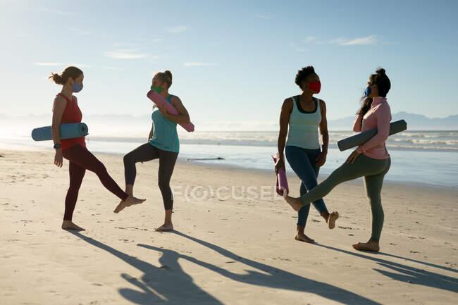 Группа разнообразных подруг в масках практикующих йогу, стоящих на пляже. здоровый активный образ жизни, фитнес на открытом воздухе и благополучие во время ковида 19 пандемии. — стоковое фото