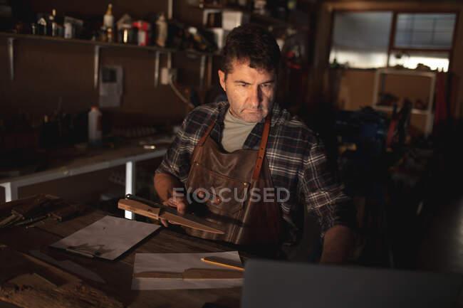 Кавказький чоловічий ножик тримає ніж, використовуючи ноутбук у майстерні. Незалежний дрібний майстер на роботі.. — стокове фото