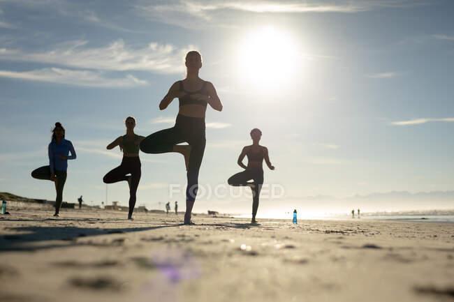Группа разнообразных подруг практикующих йогу на пляже. здоровый активный образ жизни, фитнес на открытом воздухе и благополучие. — стоковое фото
