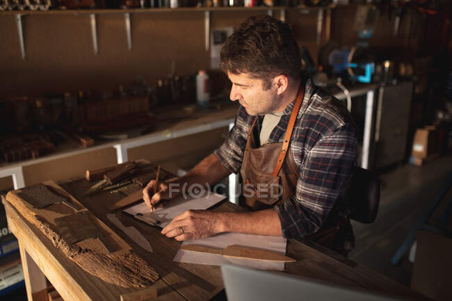 Caucasian male knife maker sitting at desk, making notes in workshop. independent small business craftsman at work. — Stock Photo