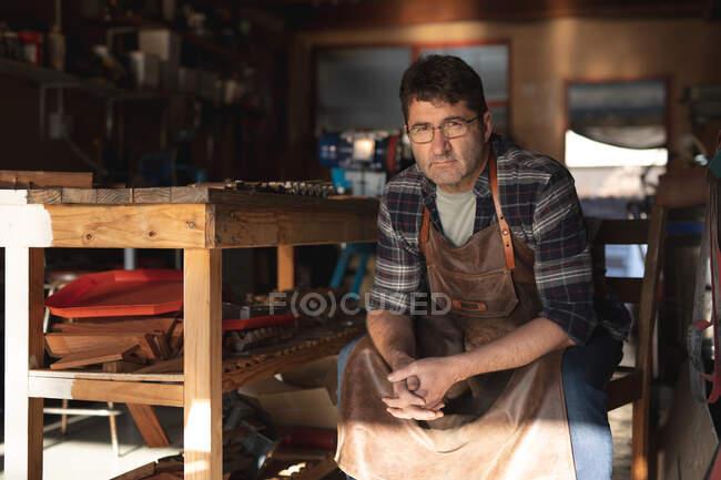 Кавказький чоловічий виробник ножів сидить на стільці, дивлячись на камеру в майстерні. Незалежний дрібний майстер на роботі.. — стокове фото