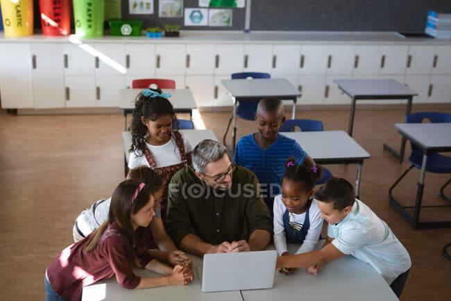 Professeur masculin caucasien et groupe d'étudiants divers utilisant ordinateur portable ensemble dans la classe à l'école. concept scolaire et éducatif — Photo de stock