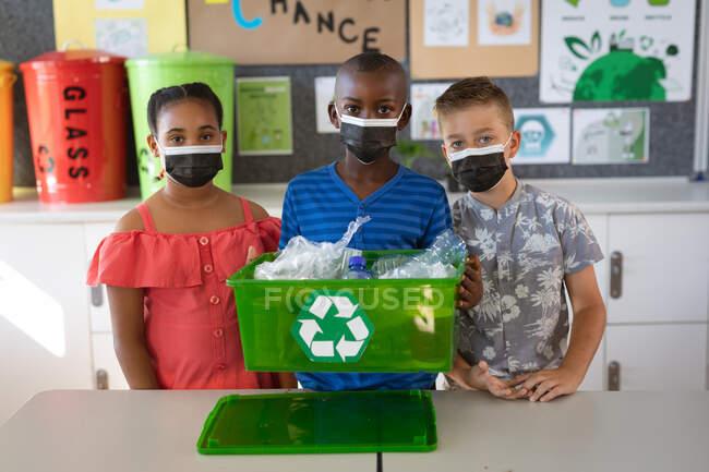 Grupo de diversos estudiantes con máscaras faciales que sostienen una bandeja llena de artículos de plástico reciclables. educación volver a la escuela seguridad sanitaria durante la pandemia de coronavirus covid19. - foto de stock
