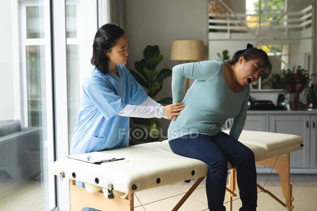 Азійка-жінка фізіотерапевт лікує вдома старшу жінку-пацієнта. Медичне обслуговування та фізіотерапія. — стокове фото