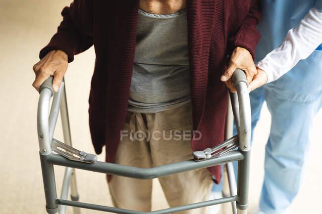 Fisioterapeuta femenina atendiendo a una paciente mayor en su casa. atención médica y fisioterapia médica tratamiento. - foto de stock