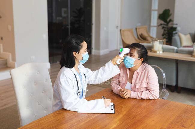 Médico asiático femenino que usa mascarilla facial y toma la temperatura de la paciente femenina en casa. atención médica y fisioterapia médica tratamiento. - foto de stock