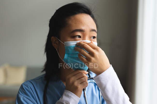 Fisioterapeuta asiática que usa mascarilla en casa antes del tratamiento. atención médica y fisioterapia médica tratamiento. - foto de stock