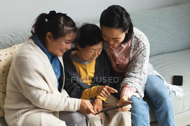 Щаслива старша азіатка вдома з дорослими донькою та внучкою за допомогою таблетки. Старший спосіб життя, перебування вдома з родиною.. — стокове фото