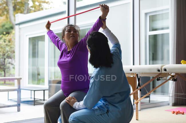 Fisioterapeuta asiática que trata a una paciente asiática en su casa. atención médica y fisioterapia médica tratamiento. - foto de stock