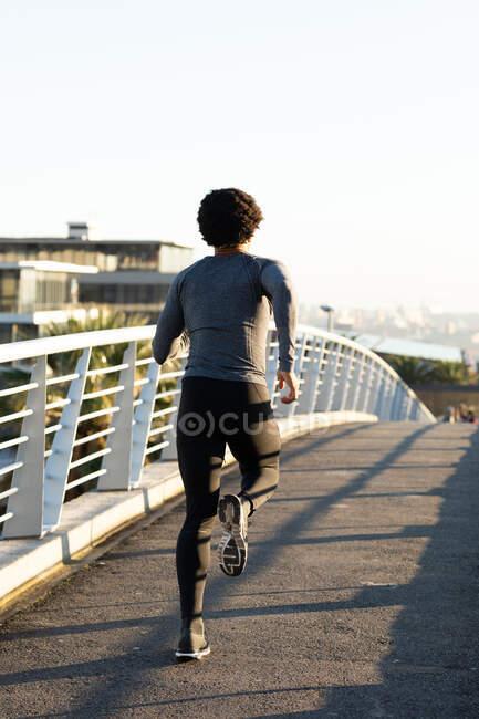 Подходящий африканский американец, тренирующийся в городе, бегущем по улице. фитнес и активный городской уличный образ жизни. — стоковое фото