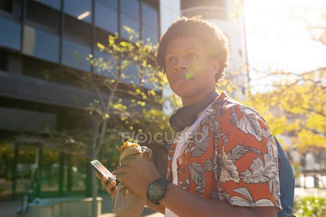 Uomo afroamericano in città che mangia e usa lo smartphone. nomade digitale in movimento, in giro per la città. — Foto stock