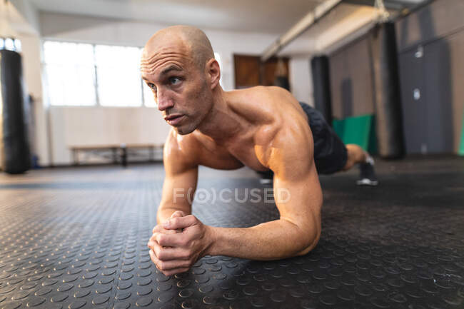 Hombre caucásico fuerte haciendo ejercicio en el gimnasio, haciendo tablón. entrenamiento cruzado de fuerza y fitness para boxeo. - foto de stock