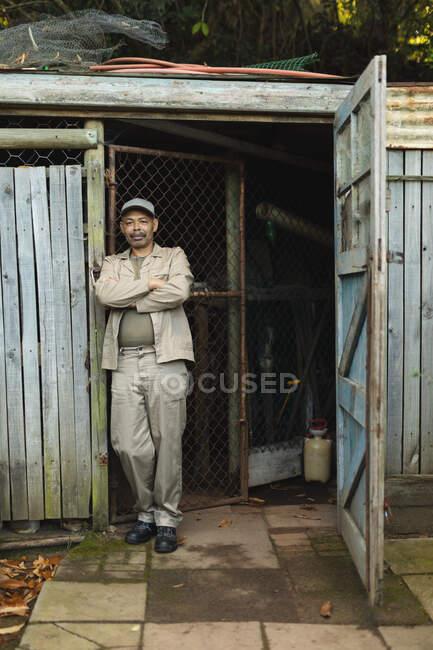 Африканський садівник-аматор з перехрещеними руками дивиться на камеру в центрі саду. Спеціаліст, який працює в розпліднику бонсай, незалежному садівництві.. — стокове фото